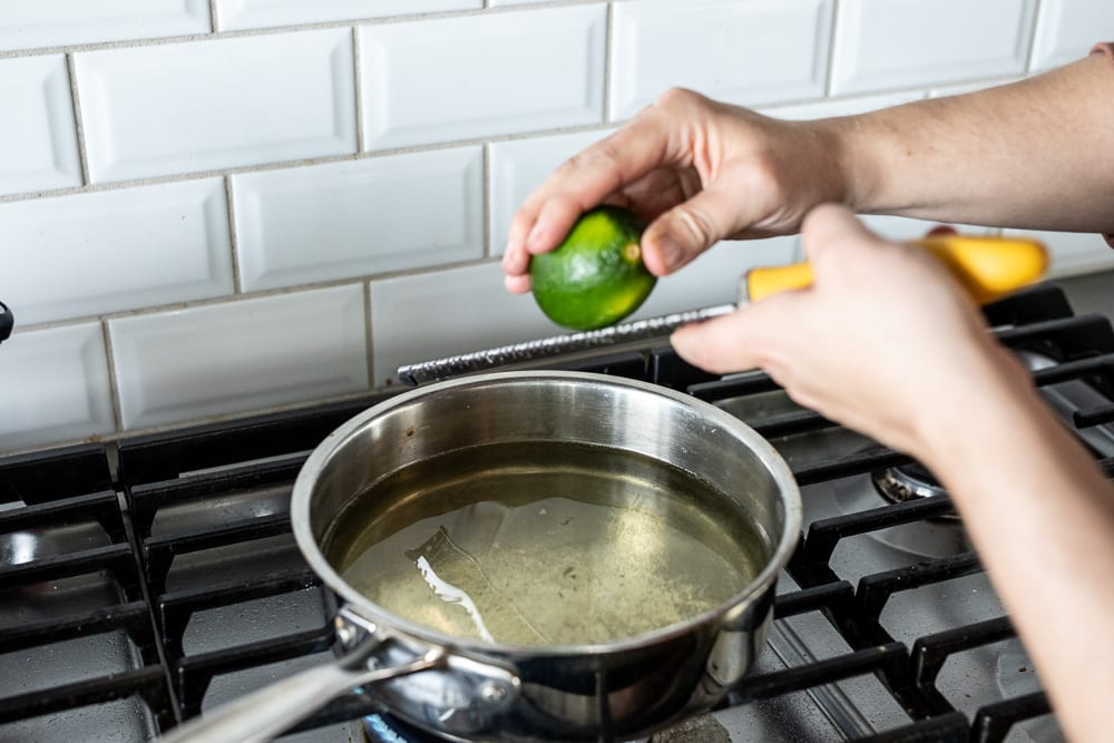 grated lime zest into vegetable stock in a stainless steel pan on gas cooktop