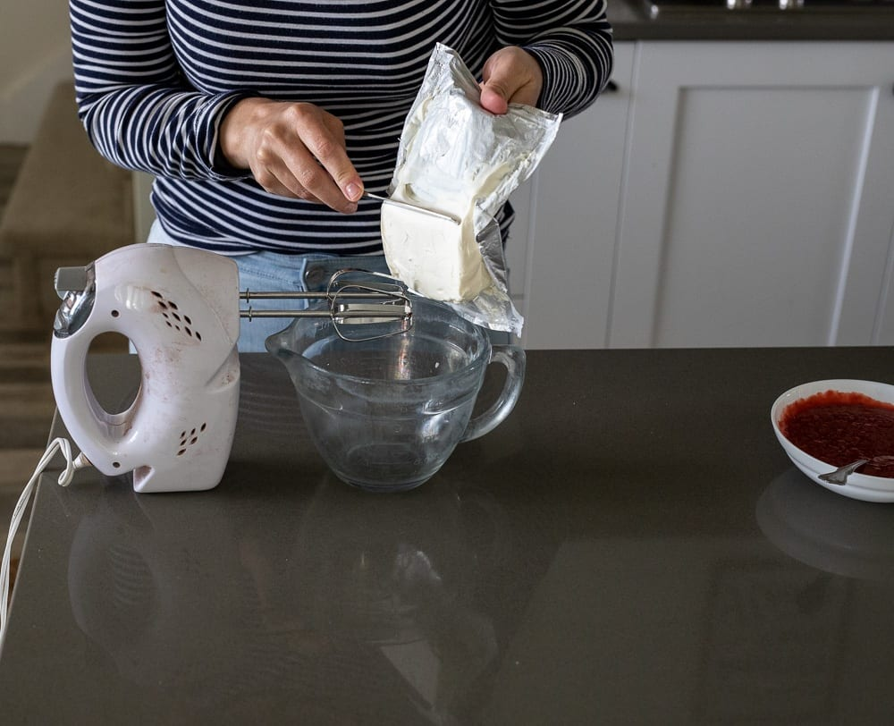 woman scraping cream cheese into glass measuring cup beside a white hand mixer