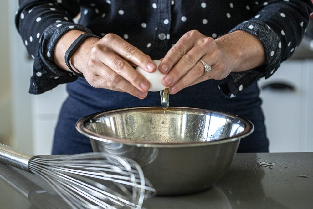 woman cracking eggs into stainless steel bowl. whisk is on the countertop near the bowl.