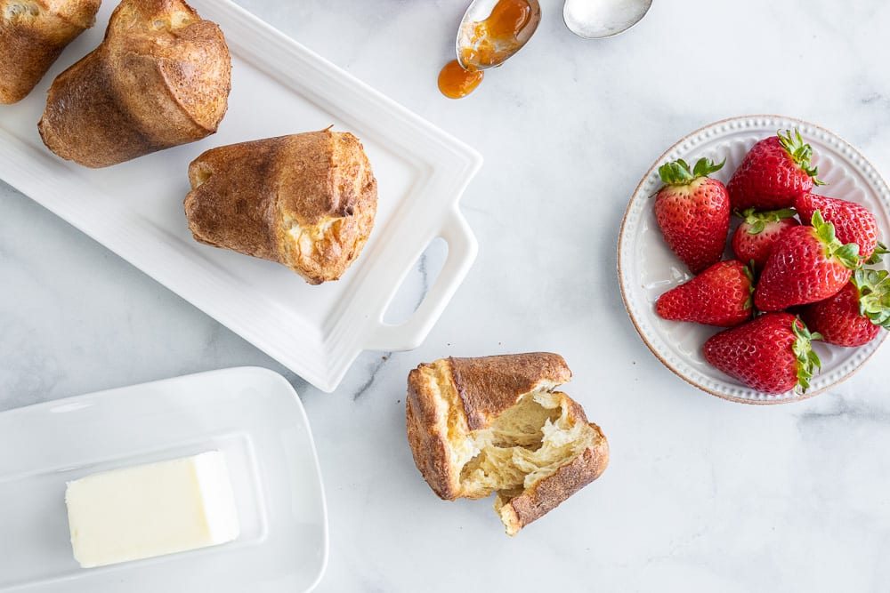 whole grain popovers laid out on white tray, small white plate with fresh strawberries. small plate butter dish and antique spoon with apricot preserves.
