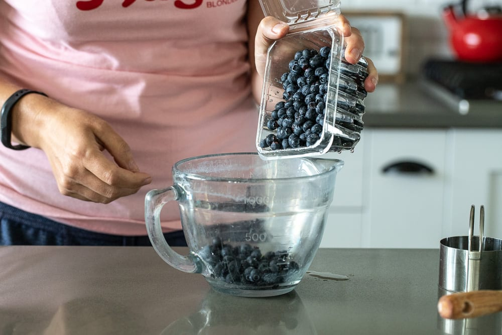 woman pouring fresh blueberries into glass 4 cup measuring container