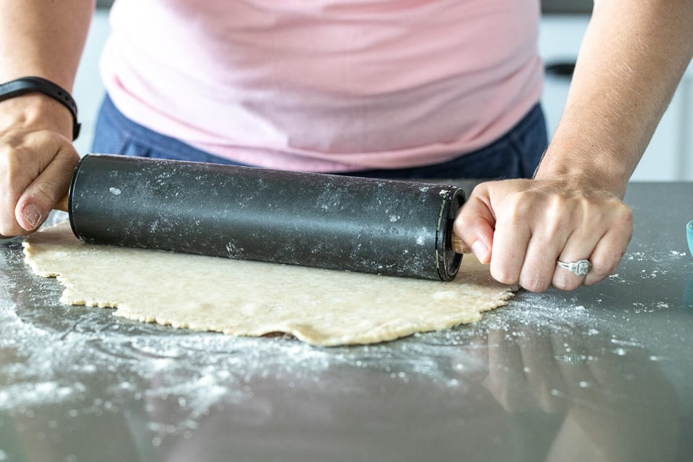 woman rolling out pie dough on floured surface