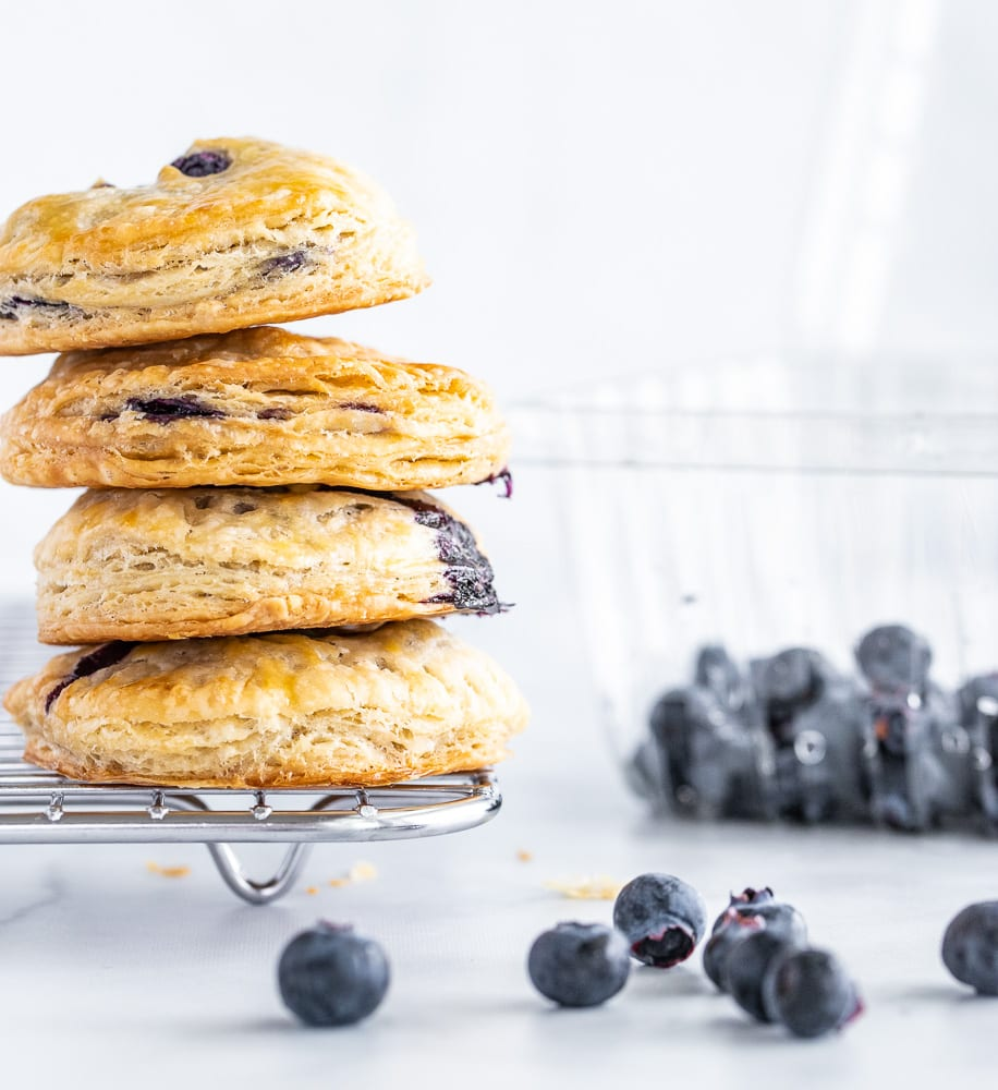 stack of blueberry hand pies on cooling rack. blueberry container in the background.