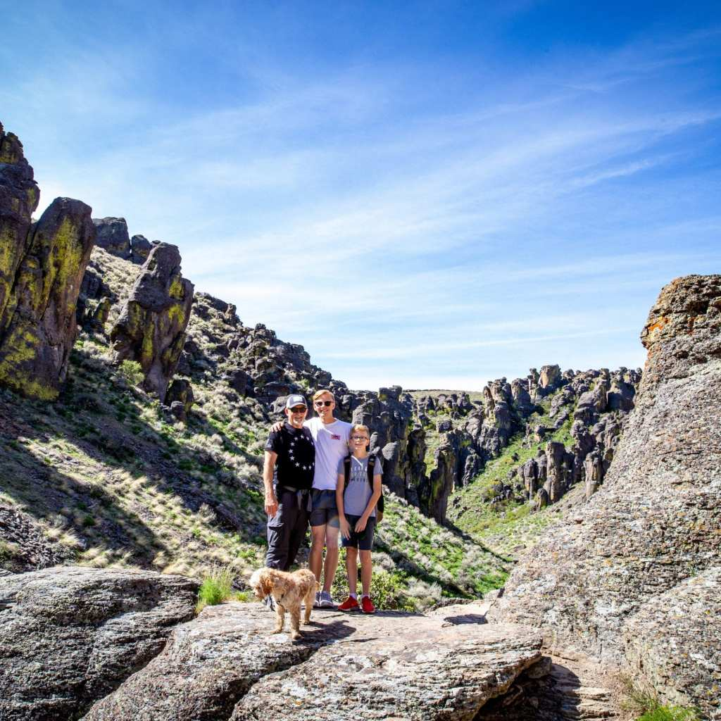 2 boys, their dad and cavapoo hiking through canyon in idaho