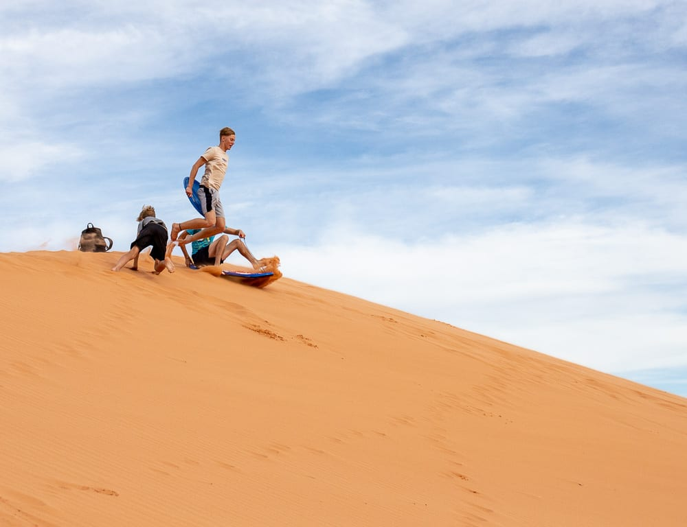 boy in air on sled on coral pink sand dunes.