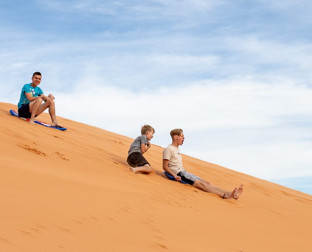 teenage boy falling onto sand dunes with sled. brother rolling behind, friend looking on.