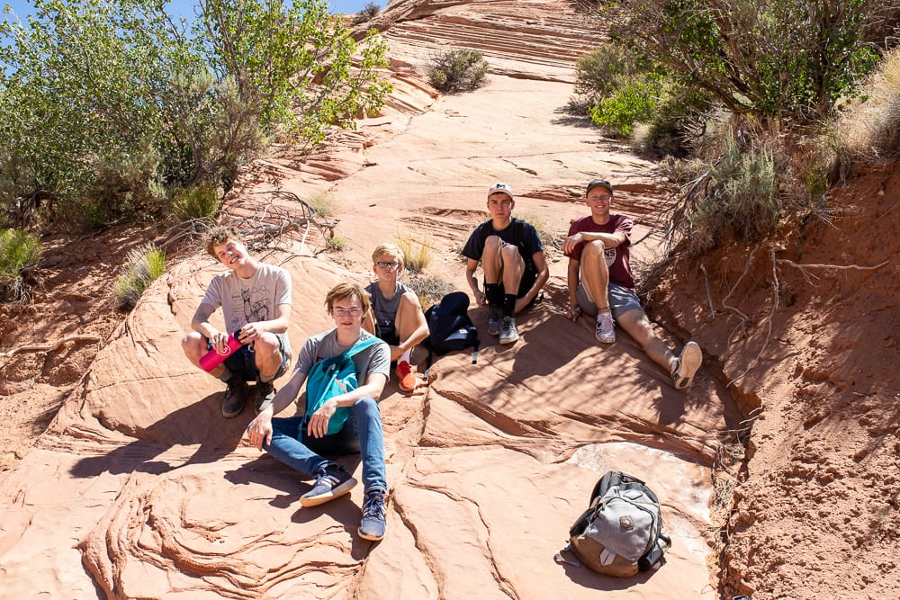 teenagers taking a break on rock in southern utah
