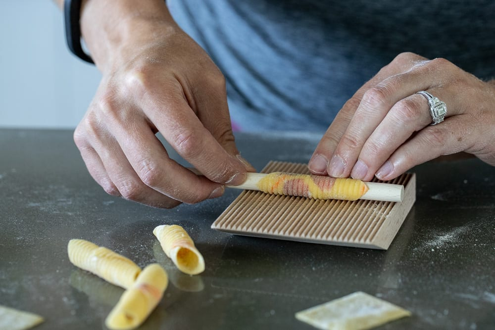 woman rolling garganelli on gnocchi grooved board with rod
