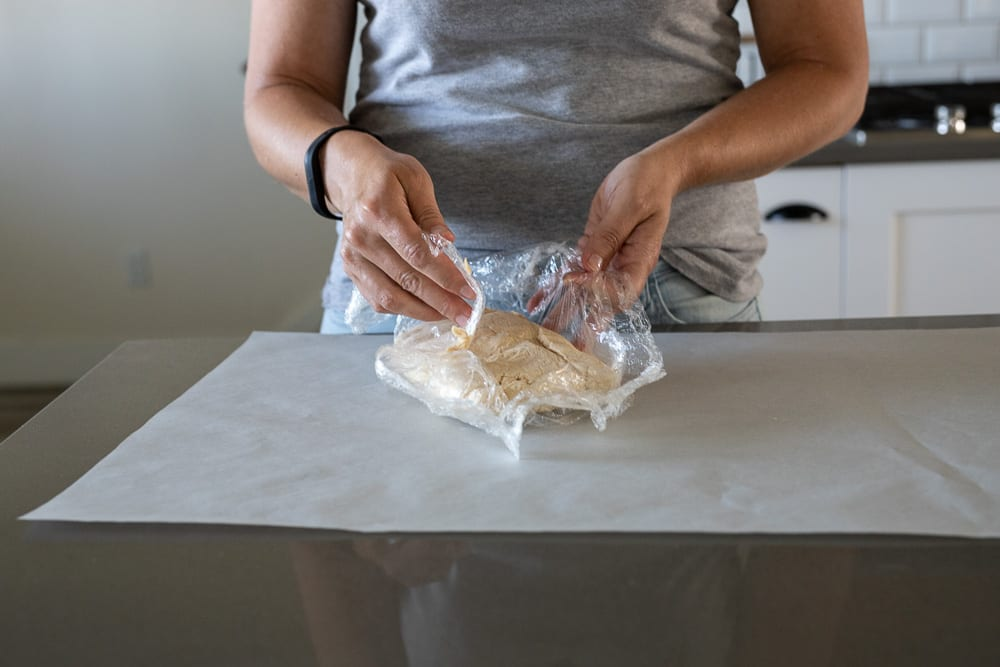 woman removing cookie dough from plastic wrap onto parchment paper