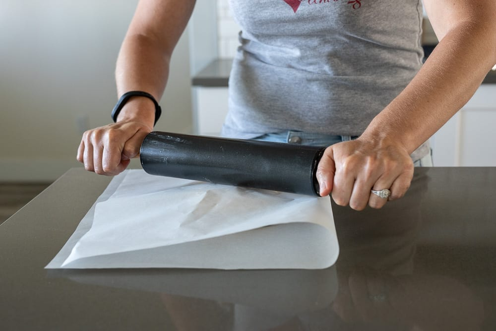 woman rolling shortbread dough between parchment paper with black rolling pin