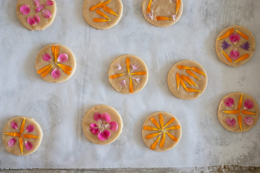 shortbread cookies with edible flowers on top, ready for baking.