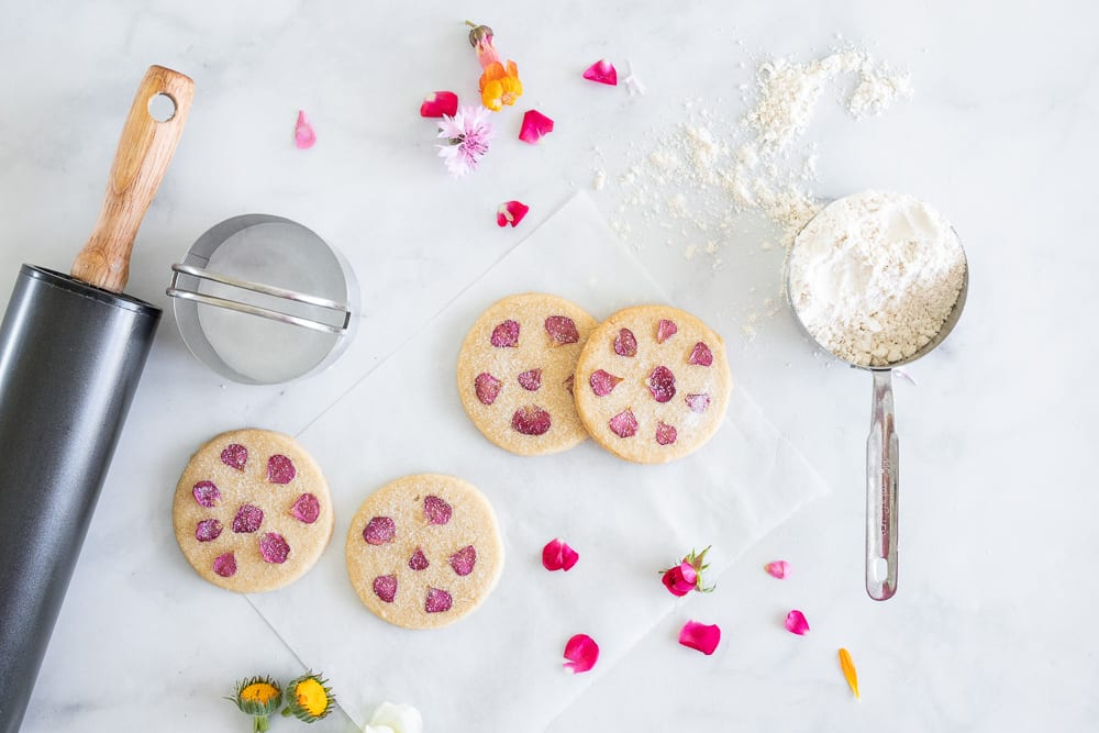shortbread cookies with edible flowers, rose petals on the counter top
