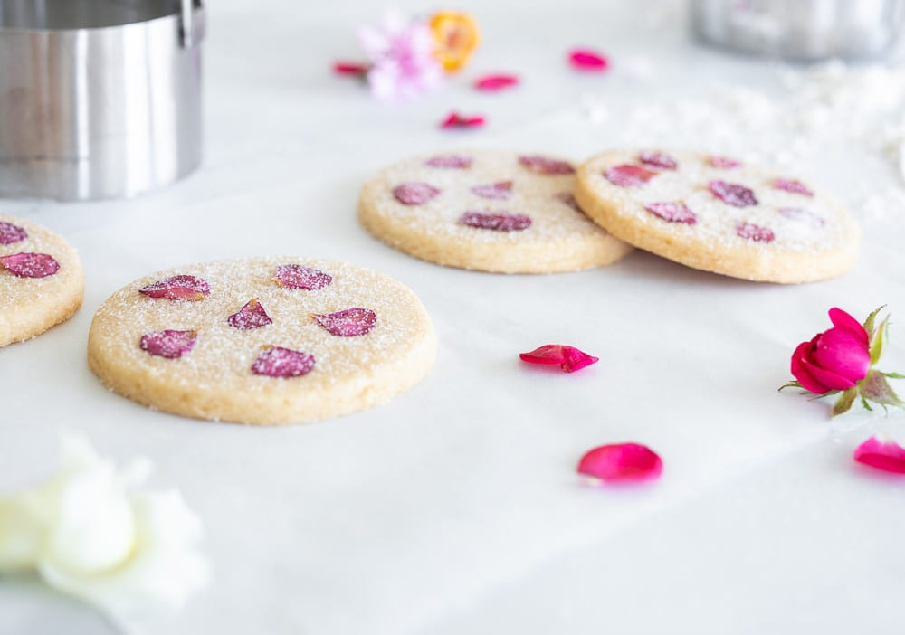 shortbread cookies with edible flowers on parchment paper with rose petals in the foreground