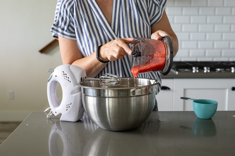 woman pouring pureed strawberries into stainless steel mixing bowl