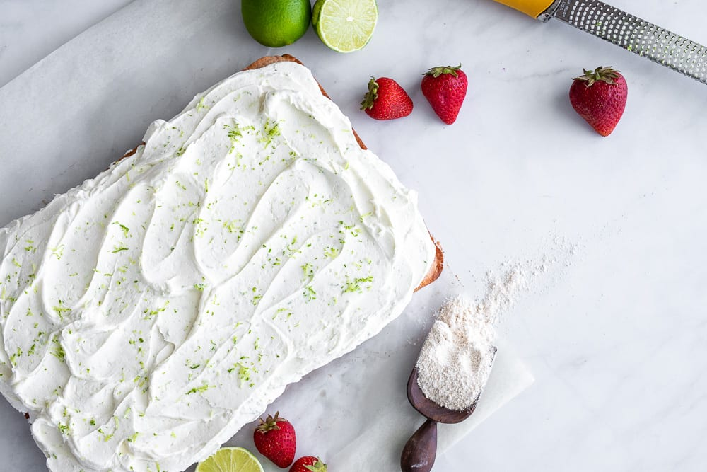 strawberry cake with lime buttercream on marble surface with fresh strawberries and lime on the surface