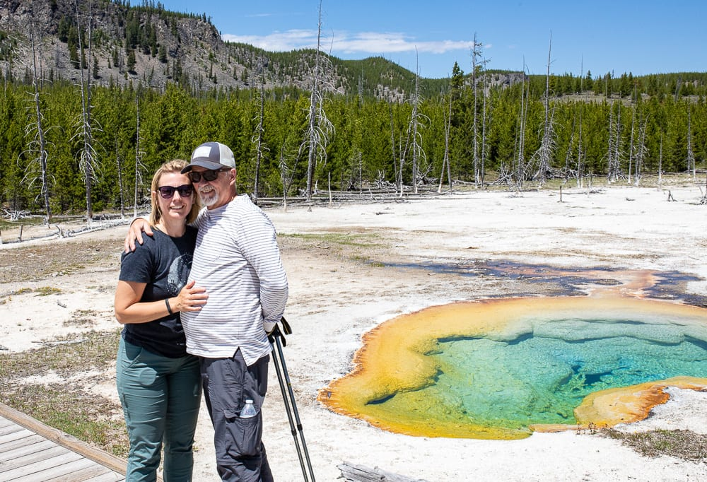 couple standing by multicolored hot spring in yellowstone national park