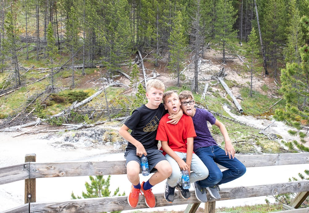 three boys sitting in front of hot springs in yellowstone national park