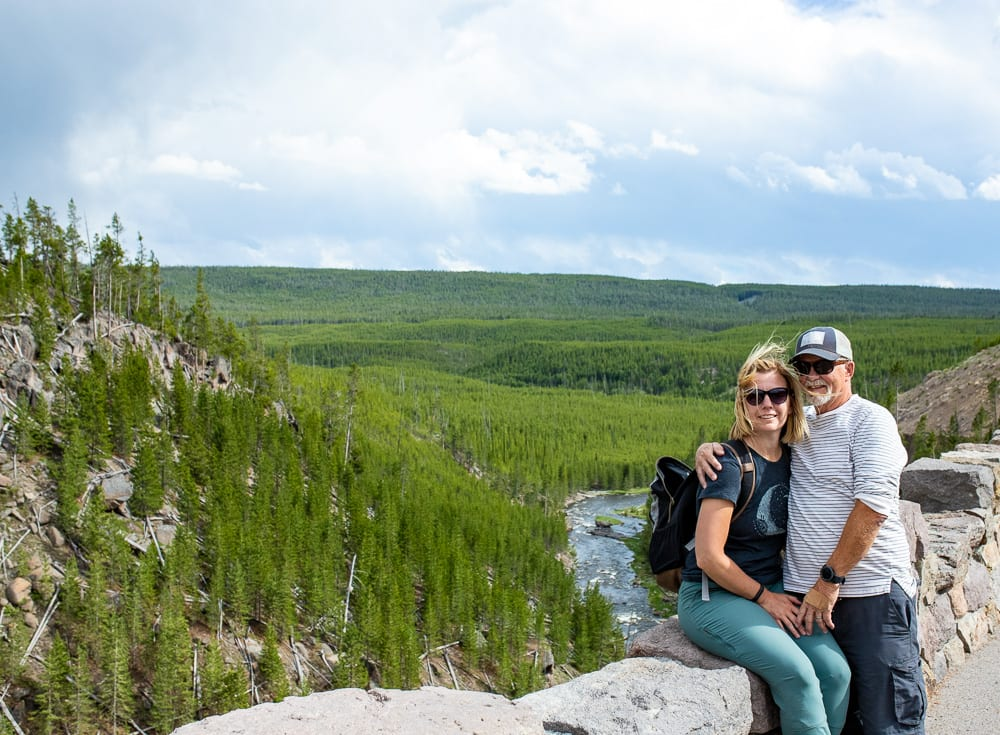 couple on an overlook with lots of trees and a river in the background