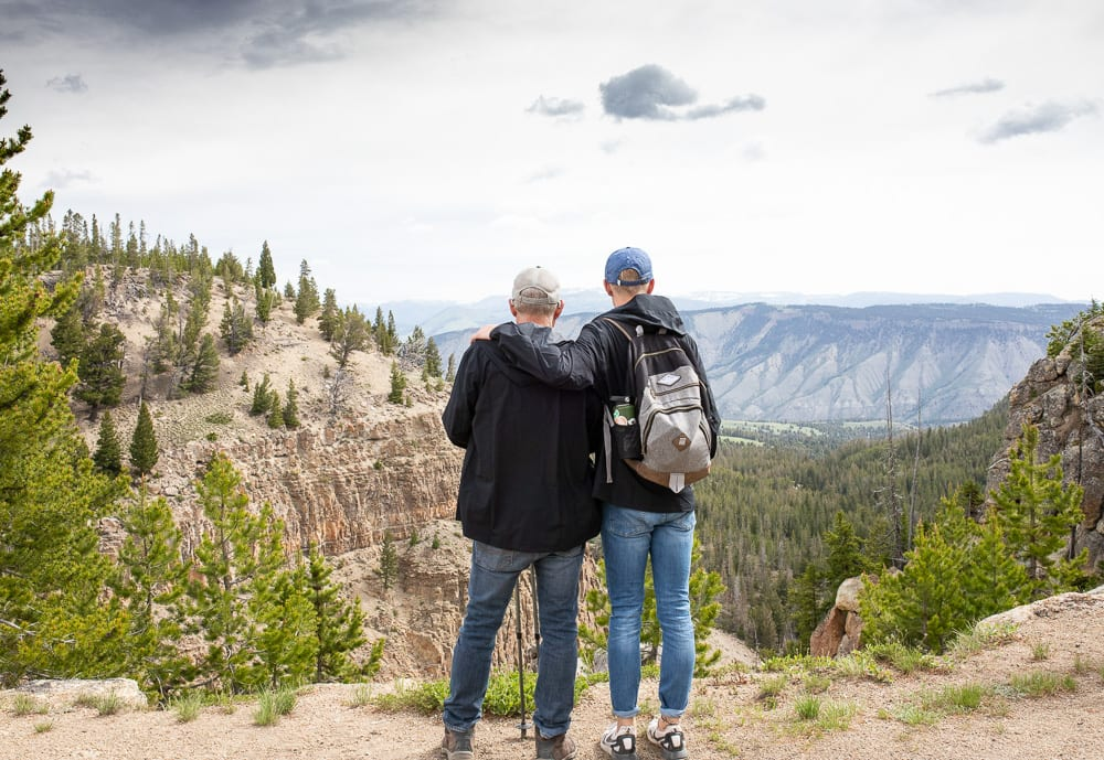 Teenage son with arm around Father in an embrace on Bunsen peak trail Yellowstone National park