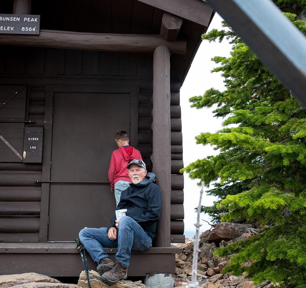 Man taking a break sitting at a cabin on Bunsen Peak Yellowstone