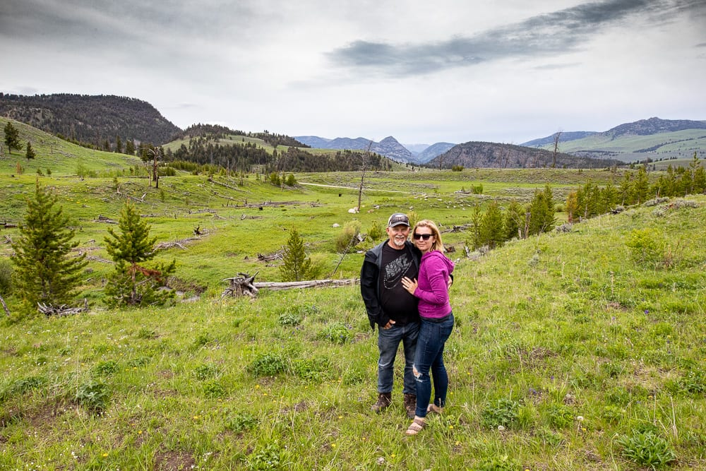 a couple stranding in a meadow with mountains in the distance. vacation at yellowstone