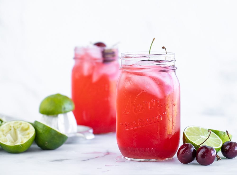 cherry limeade in mason jars. limes and cherries on countertop.