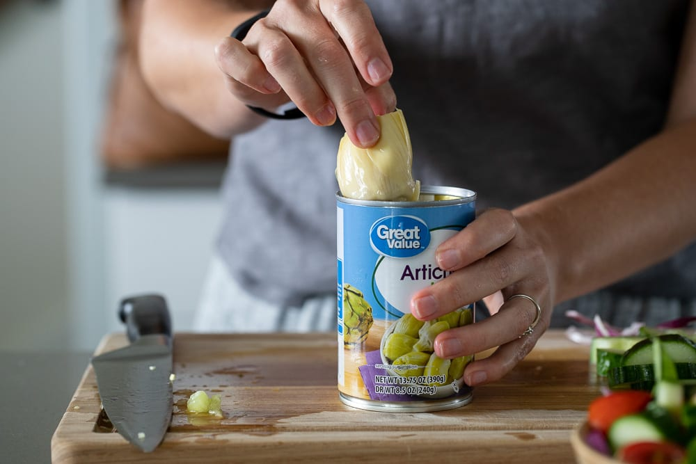 woman pulling a artichoke from can for a Italian Vegetable salad