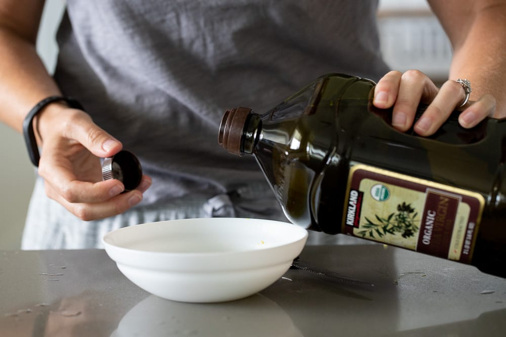 woman pouring olive oil into small white bowl on counter top