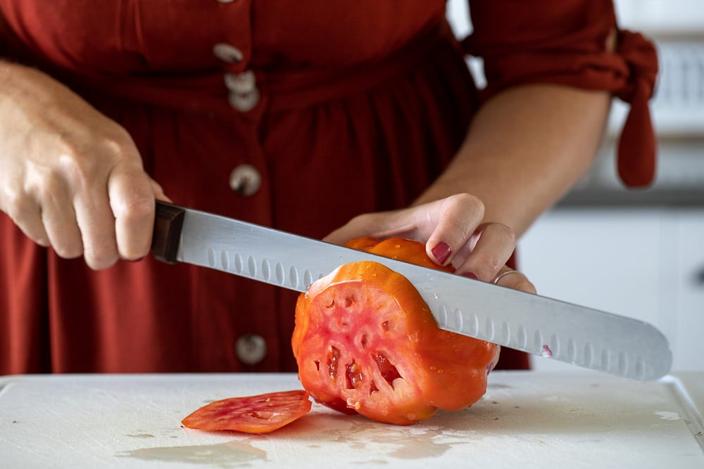 woman slicing heirloom tomatoes with a citrus knife.