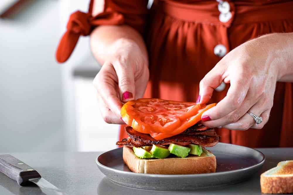 woman placing heirloom tomatoes on a blat sandwich