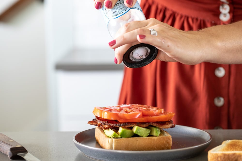 woman sprinkling salt on heirloom tomato slices for blat sandwich