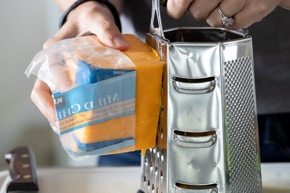 woman grating mild cheddar cheese on metal grater
