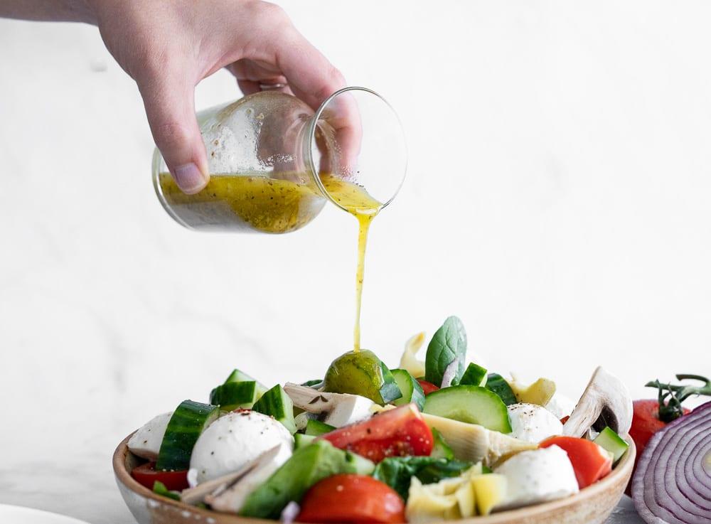 woman pouring lemon oregano dressing on italian vegetable salad.