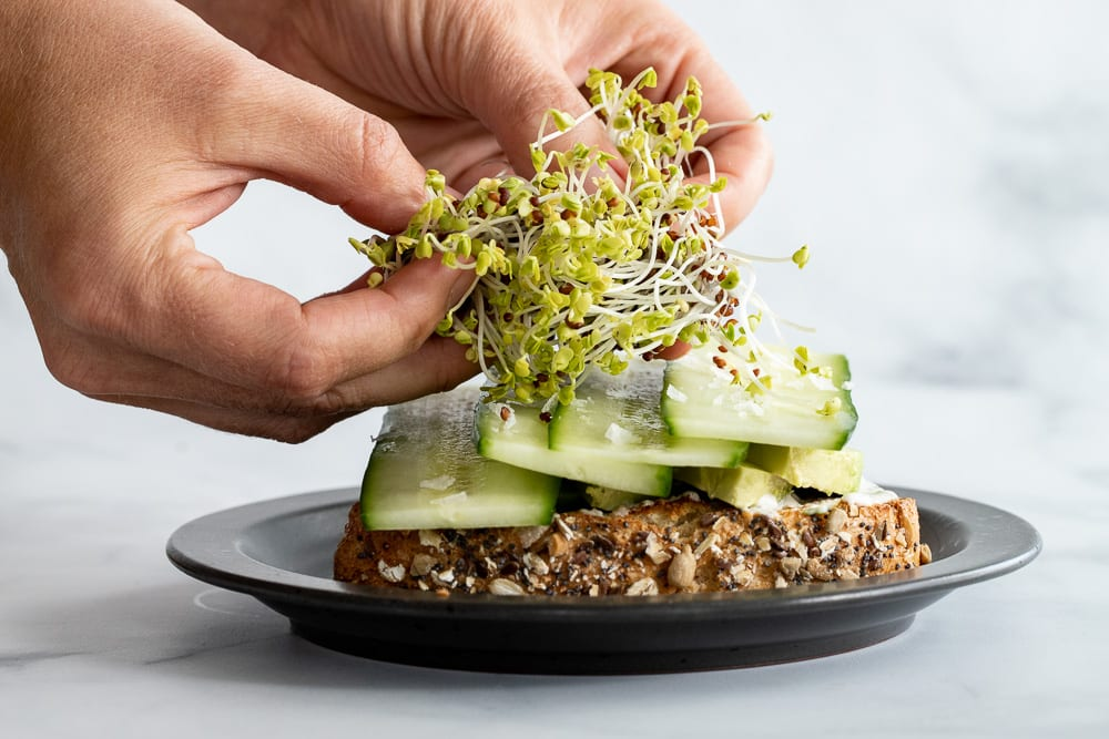 woman adding sprouts to green goddess sandwich