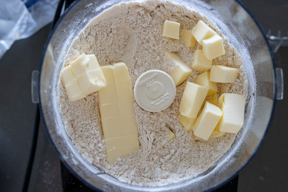 flour mixture with cold butter cubed on top in Cuisinart food processor