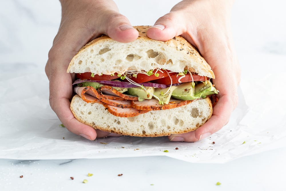 woman holding a turkey and sprouts on ciabatta sandwich