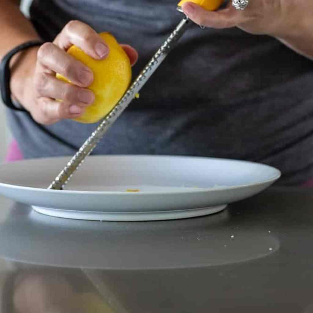 woman zesting lemon on microplane