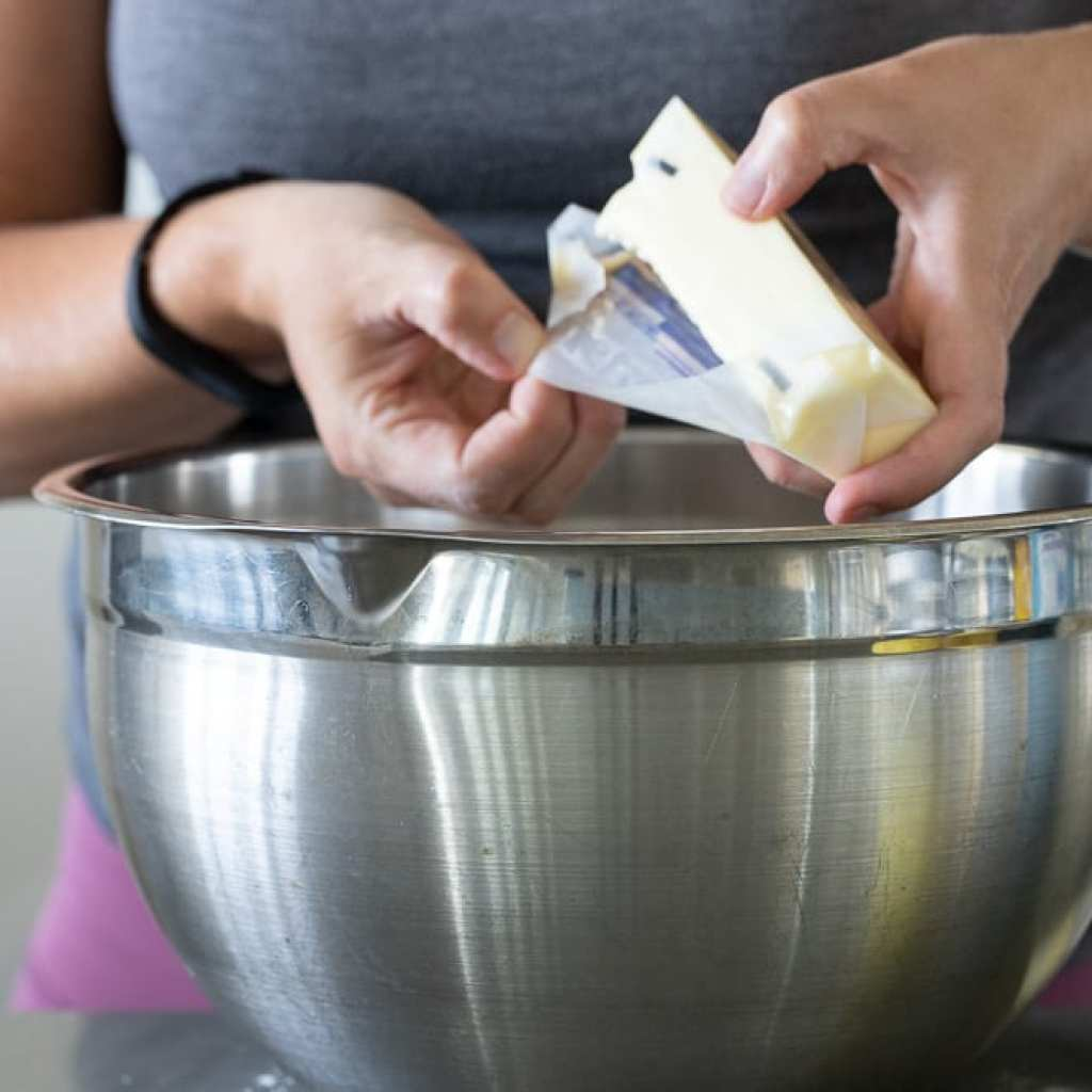 woman adding butter into stainless steel bowl