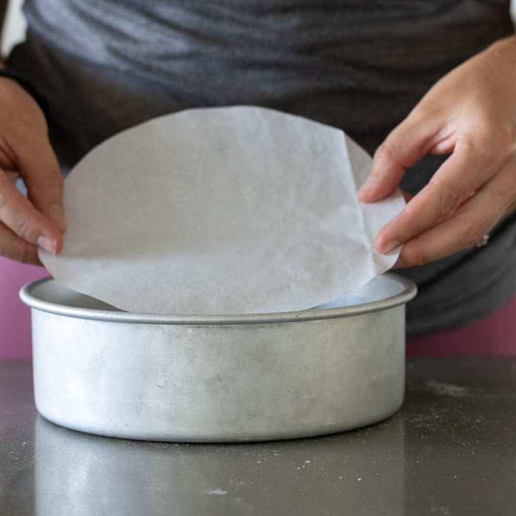 woman placing parchment circle in cake pan