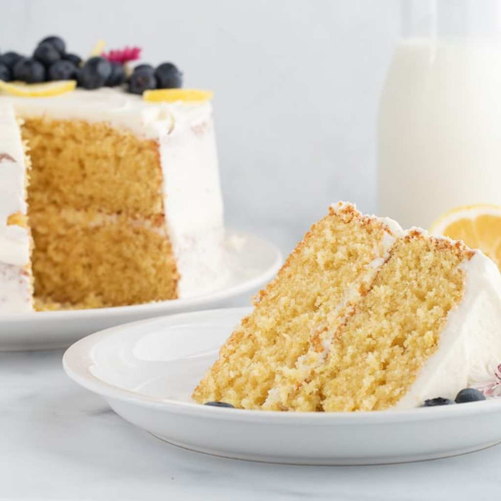 slice of the best lemon cornmeal cake with blueberries on small dessert plate