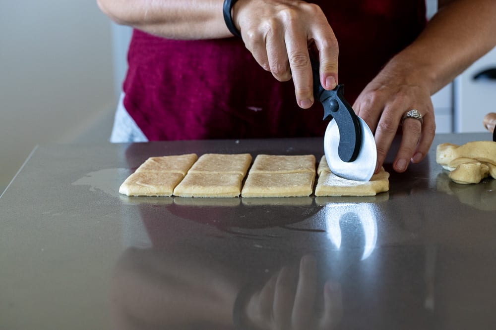 Woman cutting mandazi into triangles on a greased quartz countertop