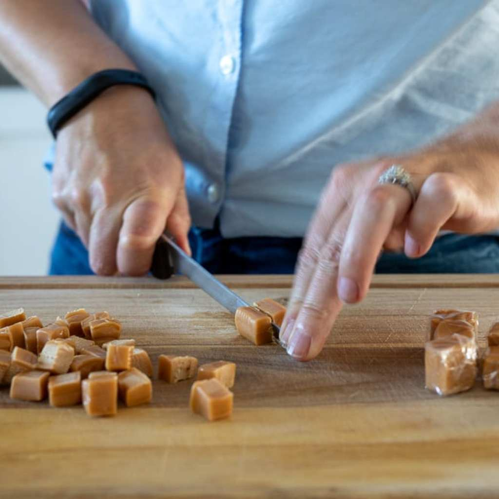 woman cutting caramels into fourths on a wooden cutting board with a boning knife
