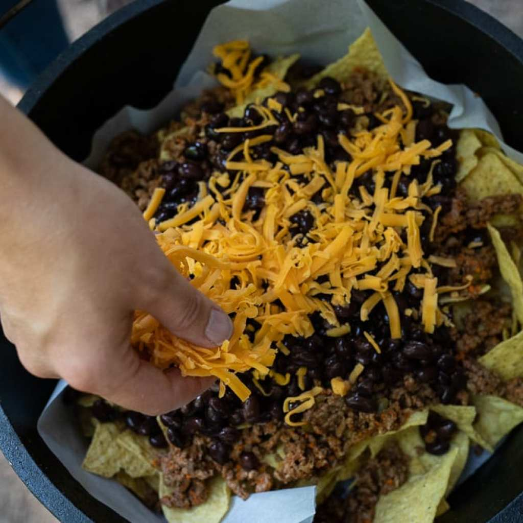 woman sprinkling grated cheese over meat and black beans in dutch oven