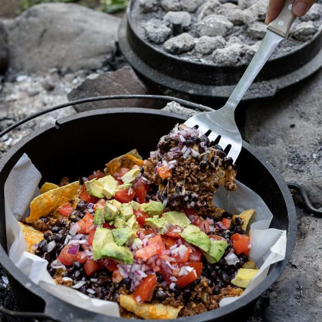 woman scooping out campfire nachos with metal spatula