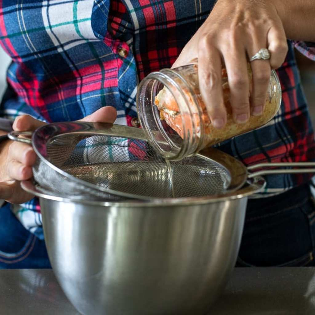 woman pouring canned salmon from mason jar into mesh strainer to drain