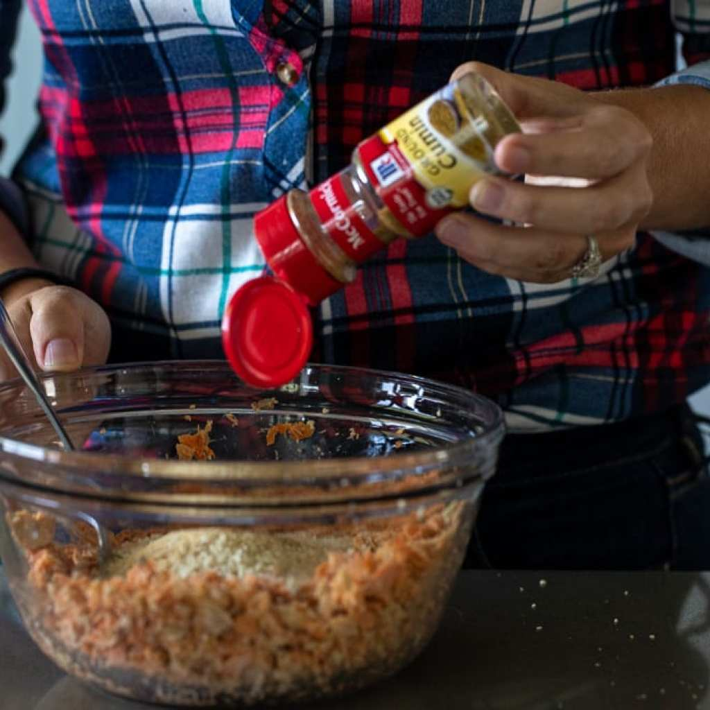 woman adding cumin to flaked salmon for salmon patty