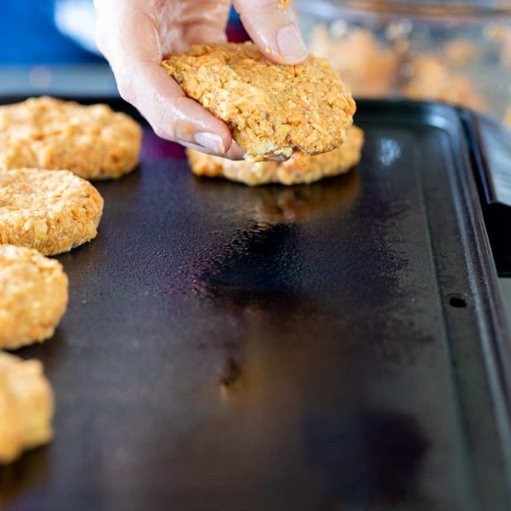 woman forming salmon patties to cook on griddle for salmon patty bowl
