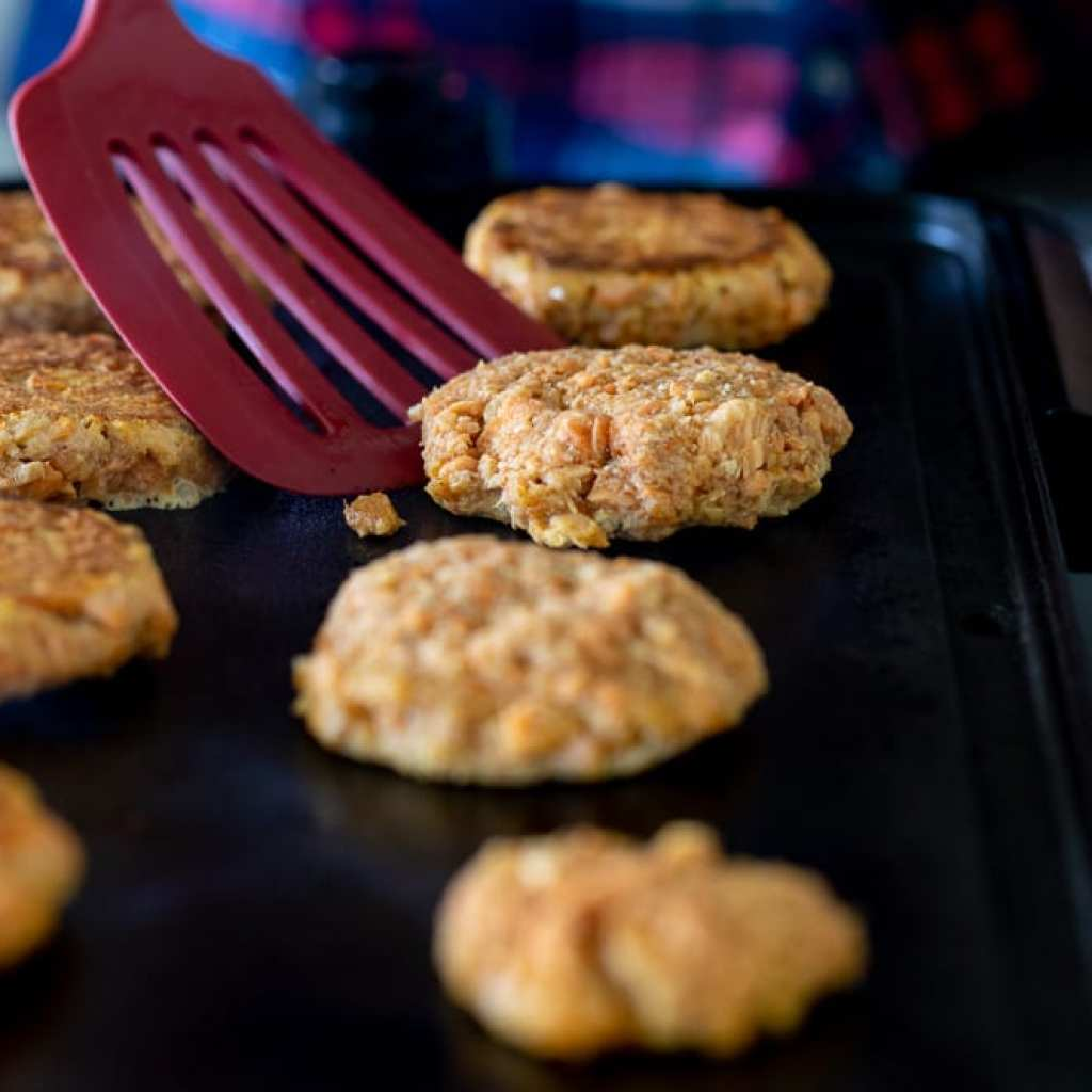 woman flipping salmon patties as they cook on a griddle