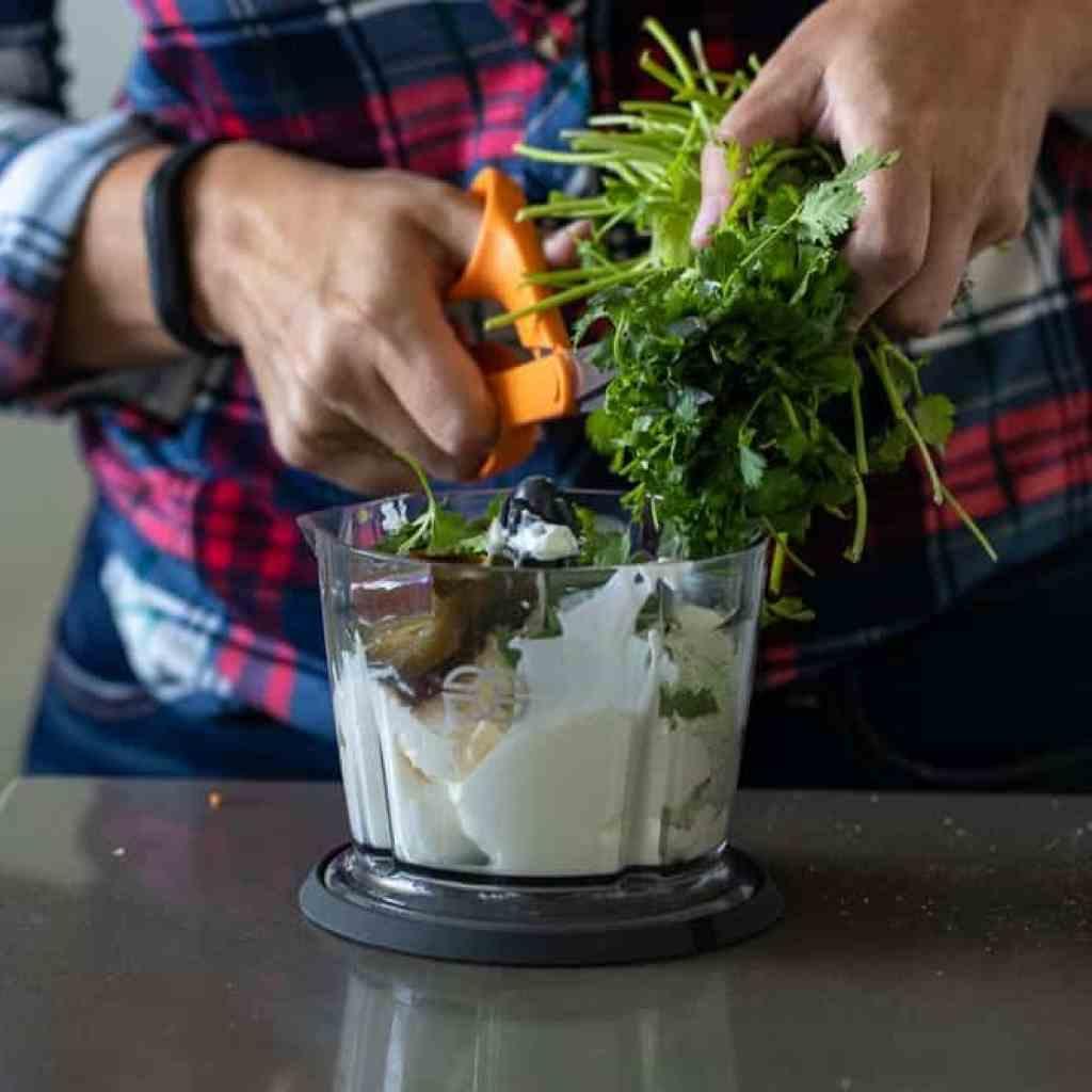 woman adding chopped cilantro to small food processor
