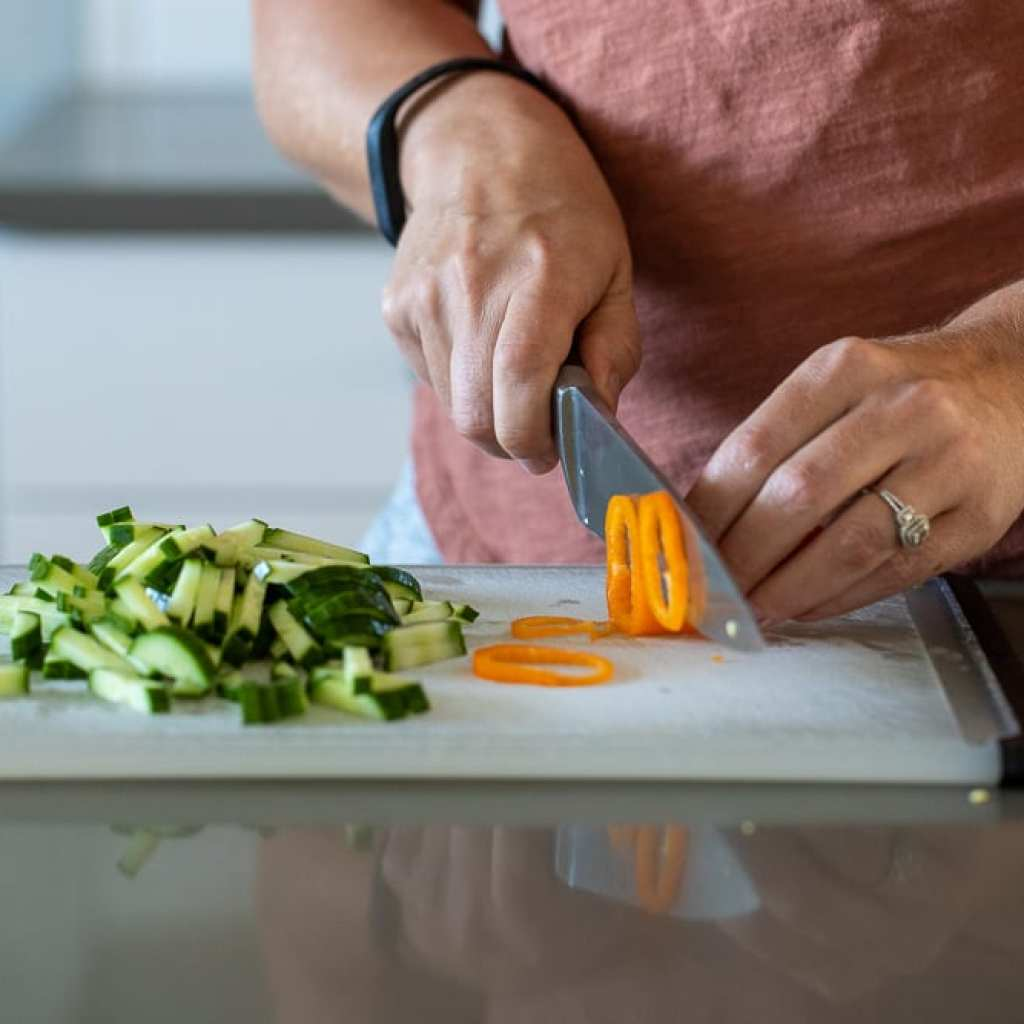 woman slicing veggies for salad